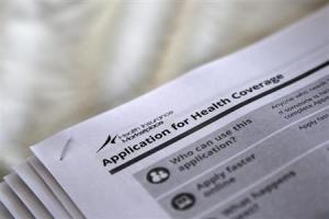 The federal government forms for applying for health coverage are seen at a rally held by supporters